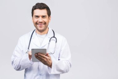 Portrait of a cheerful smiling medical doctor or nurse with stethoscope using pc tablet computer and looking at camera isolated on white background.