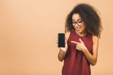 Portrait of a smiling young african american black woman holding blank screen mobile phone isolated over beige background.