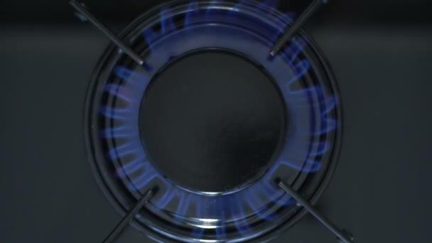 Küchenherd eingeschaltet. Herd Topflamme entzündet sich in eine blaue Kochflamme. Erdgasentzündung, Nahaufnahme, Zeitlupe.