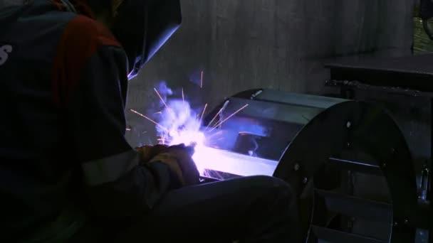 Zblízka kovář svářeč v ochranné masce pracuje s kovem pomocí svařovacího stroje, jasné jiskry. Záběry 4K