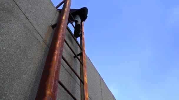 Der Mensch ist eine hohe rostige Stahlleiter hinunter. Mann steigt eine Leiter auf dem Dach eines Hauses hinunter