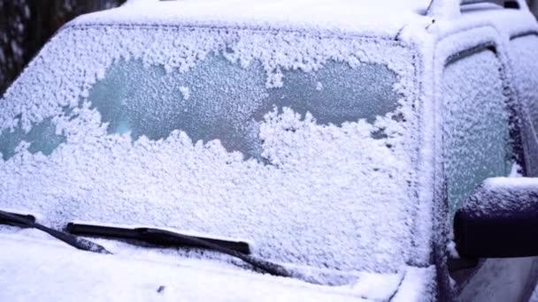 Die Frontscheibe des Autos ist mit Schnee bedeckt. Konzept der winterlichen Wetterbedingungen. Schnee auf dem Glas Nahaufnahme. Winterlicher Hintergrund