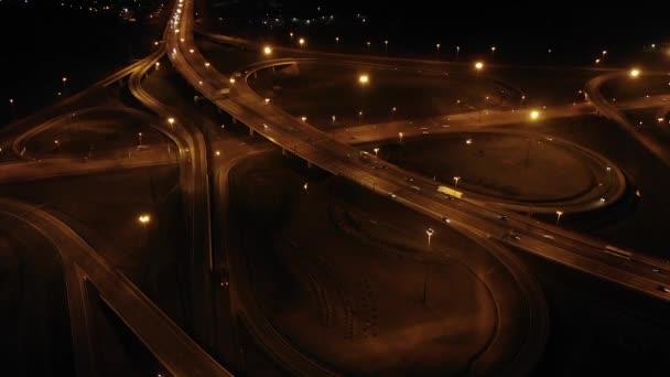 Noční letecký pohled na křižovatku dálničních spojovacích listů s rampami, hustým provozem, vzduchem. Výměna silnic s rušnou městskou dopravou