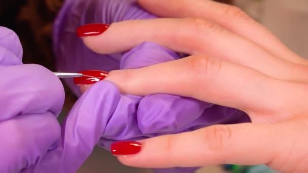 Maniküre Maniküre Client Nägel lackieren mit rotem Nagelgel Lack. Lack. Maniküre. Nagelverlängerung