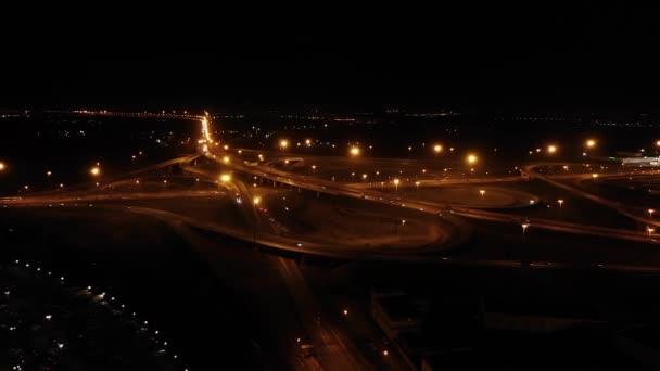 Dálniční křižovatka s jetelovými listy. Noční křižovatka s rušným provozem. Silný provoz, letecký provoz
