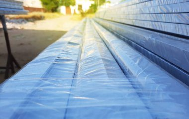 Anodized aluminium metal frames wrapped in polythene in a factory with selective focus