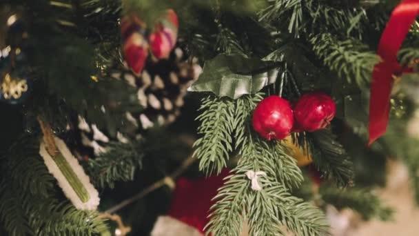 Closeup nazdobený vánoční stromeček. Červené a zlaté kuličky a osvětlená věnec s baterkami.