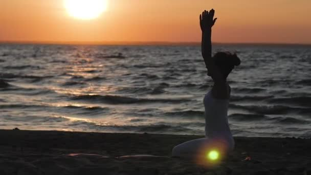 nő a tengerparton, a háttérben a víz és a naplemente, a sziluettje a jóga. Kundalini jóga