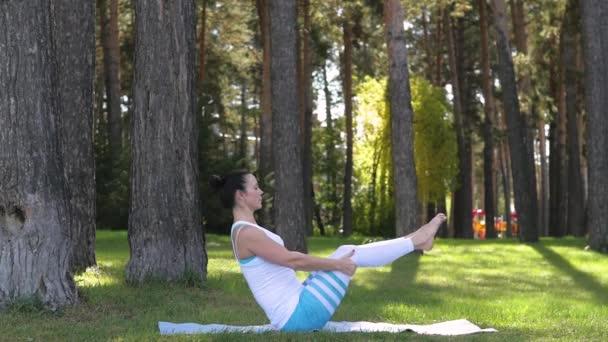 mladá žena dělá jógu v parku pod širým nebem. zdravý životní styl