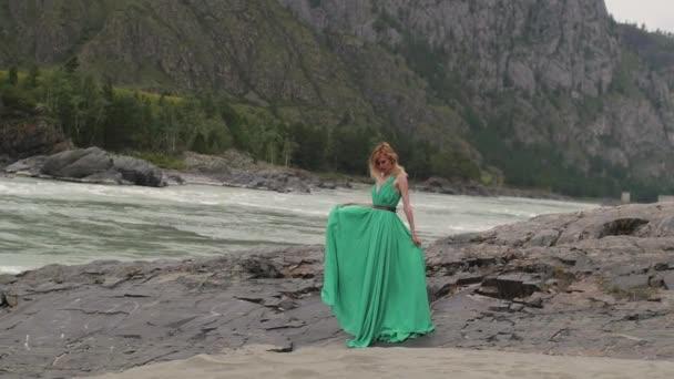 fiatal nő, egy hosszú, áramló ruhát, a háttérben a folyóra és a hegyekre. Színezés a nő körözött egy zöld ruha, a gyönyörű táj a háttérben. nő mozog, a folyó közelében