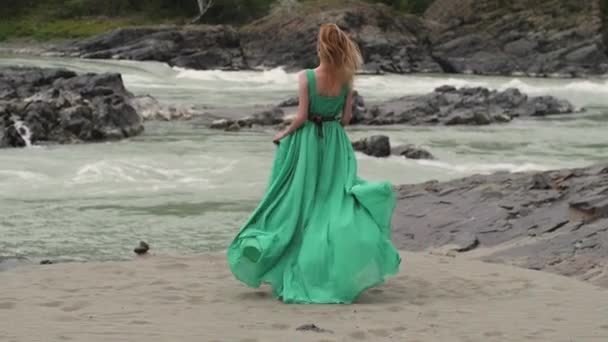 fiatal nő, egy hosszú, áramló ruhát, a háttérben a folyóra és a hegyekre. színezés a nők megy zöld ruha a háttérben a gyönyörű táj. egy nő sétál egy folyó mellett. puha
