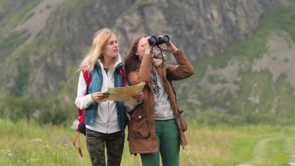 young women travel in the mountains. using the map and binoculars. two friends travel together. two girls the travelers are walking along the road against the background of the mountains