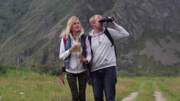 couple in love travels in the mountains with a map and binoculars. friends travelers are looking for directions on the map. man and woman tourists in the mountains. couple of travelers with a map