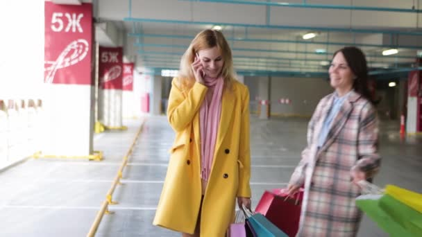 Mladá blondýnka ve žlutém kabátě s mobilním telefonem randí s přítelem. kamarádům s nákupem a taškami je na telefonu selat. online nakupování.