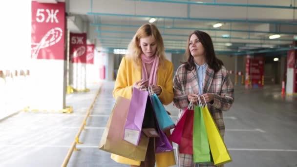 mladé ženy se zavazadly mají po nakupování radost. ženy s více barevnými sáčky v blízkosti obchodu. prodej v obchodech. nakupující, kteří se dívají na ostatní nákupy
