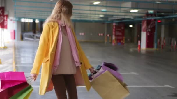 young woman with bags rejoices after shopping. a blonde woman with multi-colored bags next to the store. sale in stores. customers are going to their purchases. online shopping. a woman in a yellow
