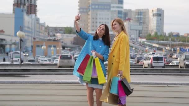 dva přátelé se setkali poblíž obchodu s pytli s více barvami. dvě ženy si po nakupování berou selu. přátelé se setkali na prodej. dvě dívky s mobilním telefonem