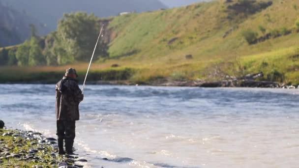 Rybář chytá ryby na pozadí horské krajiny. rybář v horské řece. Hobby muži rybář. dospělý člověk rybařit časně ráno