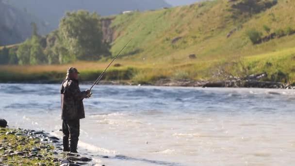 Halászlé hal a háttérben egy hegyi táj. Halász turista üvölt egy hegyi folyón. Hobbi férfiak halász. kora reggelig halászott felnőtt ember