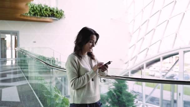 fiatal nő üzletasszony beszél egy mobilon. Egy diák telefonnal a szobában. A női ügyvéd telefonon keresztül oldja meg a kérdéseket. fiatal nő egy szobában egy telefonnal a kezében.