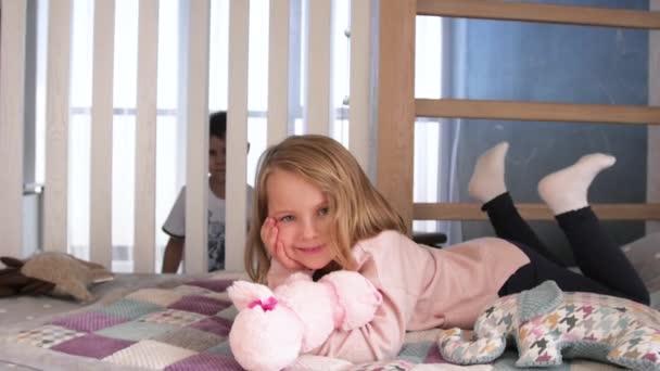Boldog gyerekek játszanak a fehér hálószobában. Kisfiú és lány, testvér játszik az ágyon visel pizsama. Család otthon