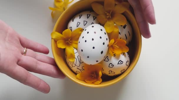 Yellow cup on a white background with Easter eggs. female hands move the cup with the eggs on the table. easter eggs in a yellow cup. White eggs with black pattern. Yellow flowers decorate Easter eggs