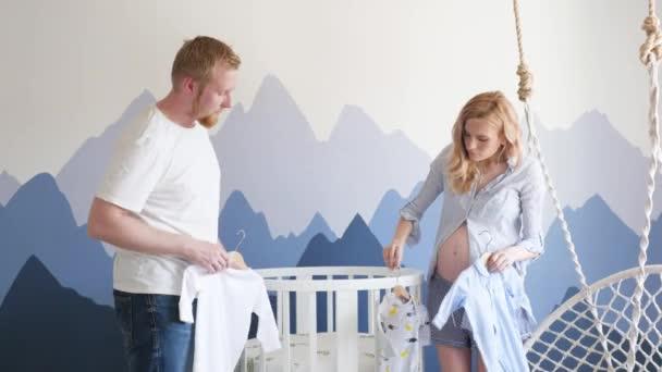 fiatal család gyűjt egy bölcsőt a meg nem született gyermeknek a hegyek között. Egy terhes nő és a férje kiságyat gyűjtenek. Skandináv stílus