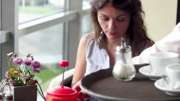 Žena čte menu, sedí u stolu na letní terase restaurace