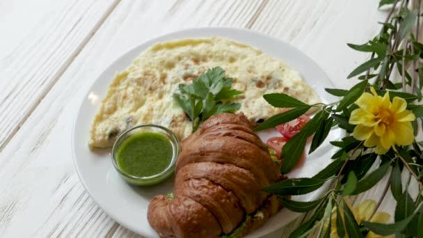Frühstück mit frischem Croissant und Omelett. Frühstück steht auf einem hölzernen weißen Hintergrund mit Blumen.