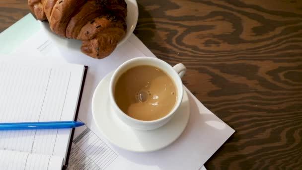 Koncept obchodního plánování. Notepad, tužka, croissant a káva na dřevěném pozadí.