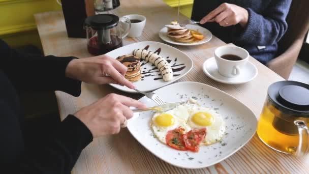 dvě ženy u snídaně jedí míchaná vejce a palačinky zblízka. společná snídaně mezi kamarádkami