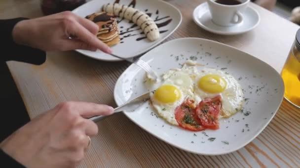 ženské ruce zblízka vidličkou a nožem přes míchaná vajíčka. žena snídá, zblízka. Jednoduchá a lahodná snídaně mini klobás Bratwurst, vajec míchaných se sýrem, toustem a černou