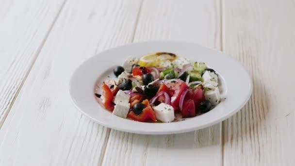 řecký salát v bílém talíři na dřevěném bílém talíři. ženská ruka s vidličkou zblízka.