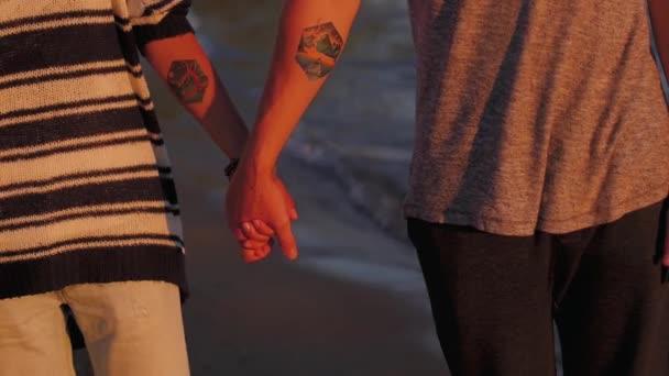 fiatal pár nő és férfi a homokos parton naplementekor. kezeket közel.