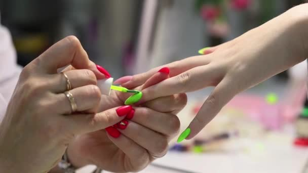 Profesionální manikúra. Prodloužení nehtu. Nanášení hlavní zelené barvy leštěného nehtu s tenkým štětcem na připravený podklad. Postup pro vytvoření gelových hřebíků v moderním salonu krásy.