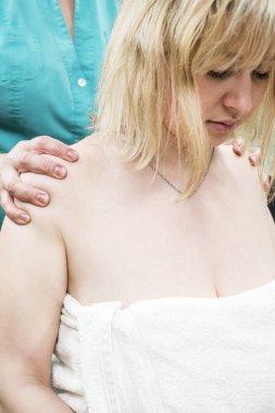 Doctor massages the patient shoulders