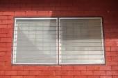 Üveg ablak a vörös téglafal háttér.
