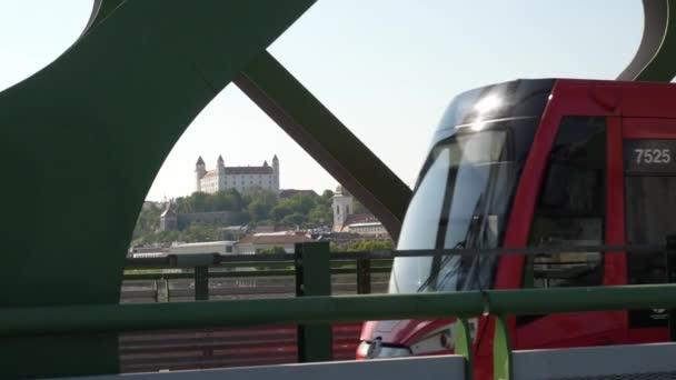 Tramvaj projíždějící na mostě v Bratislavě s výhledem na Bratislavský hrad