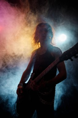 Young man with long hair with electric guitar in neon lights. Rock musician plays in atmosphere of stage