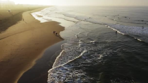 Surfers enter the water at dawn in California