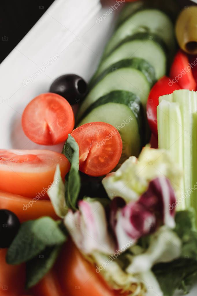 Close up food image of vegetables salad on white plate. Macro food photography of healthy meal. Focus on tomatoes