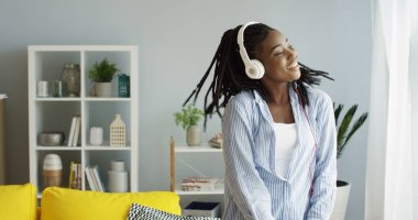 Beautiful young cheerful African American woman dancing in the rhythm of music she listening in the headphones. At home. Inside