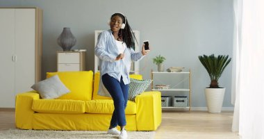 Happy young African American woman in the jeans and shirt dancing nice in the living room while listening to the music on the smartphone. Indoor