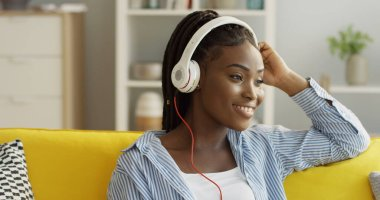 Portrait of the young smiled African American woman wearing headphones listening to the music on the yellow couch at home. Indoors