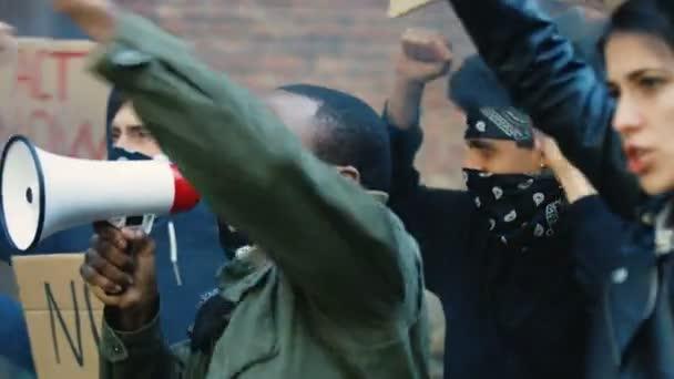 Mužští a ženské míšenci křičí slogany a protestují v USA proti rasismu a policejním aktům. Africký Američan vede a křičí v megafonu a běloška drží plakát.