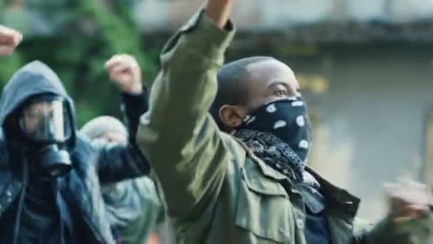 Mužští a ženské míšenci křičí slogany a protestují v USA proti rasismu a policejním aktům. Afroameričan vede a křičí, aby vedl dav.