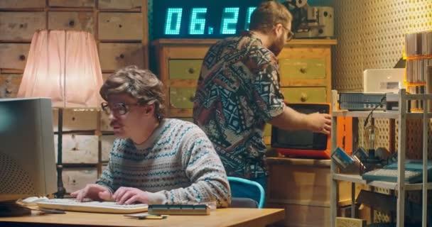Kaukázusi ideges számítógép programozó stréber szemüveges dolgozik vintage PC monitor és beszél a barátjával. 90-es évekbeli stílusú szoba. Egy férfi a háttérben, akinek gondjai vannak a régi rossz TV-vel. Férfi 80-as évek