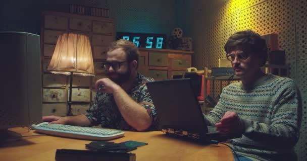 Kaukasische männliche Nerds sitzen am Schreibtisch im Retro-Raum und arbeiten an Computern. Zwei Programmierer tippen während des Studiums auf Tastaturen. Vintage-Stil der 90er Jahre. Freunde aus den 80er Jahren.