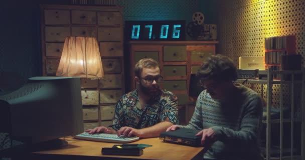 Junger Mann aus dem Kaukasus kommt mit einem alten Laptop zu Freunden und zeigt etwas auf dem Bildschirm. Männliche Nerds sitzen am Schreibtisch mit Computer und unterhalten sich im Retro-Raum. Bitten um Hilfe.