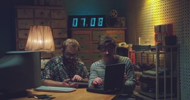 Kaukasische männliche Nerds sitzen am Tisch, reden und arbeiten am Computer. Zwei Retro-Männer tippen auf Tastaturen, studieren und zählen mit Taschenrechner. Vintage-Stil der 90er Jahre. Hacker der 80er Jahre.